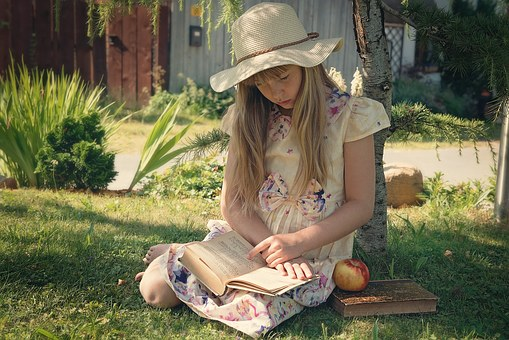 Girl sitting in garden reading book by Meria Chand